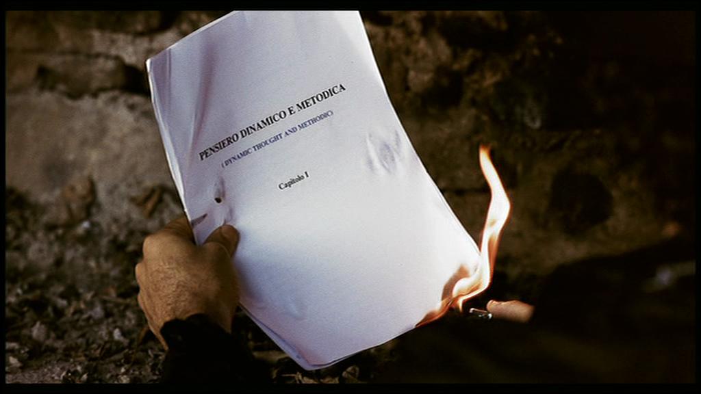 Nella baracca sul fiume il professore si scalda bruciando una copia del suo ultimo trattato
